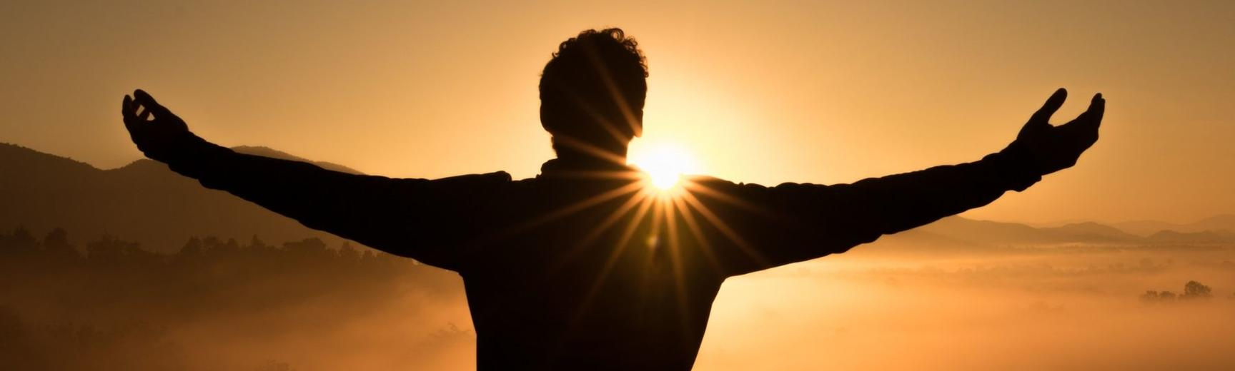 Person standing with their arms open in front of the sun