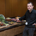 Member of staff in front of the salad bar in the Dining Hall