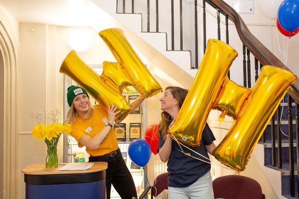 Admissions - web cover image of two people holding a W and H shaped balloons